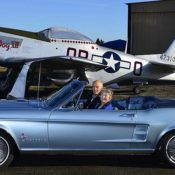 Two people sitting in a blue 1965 classic Ford Mustang convertible, parked in front of a silver and red P-51 Mustang fighter plane.