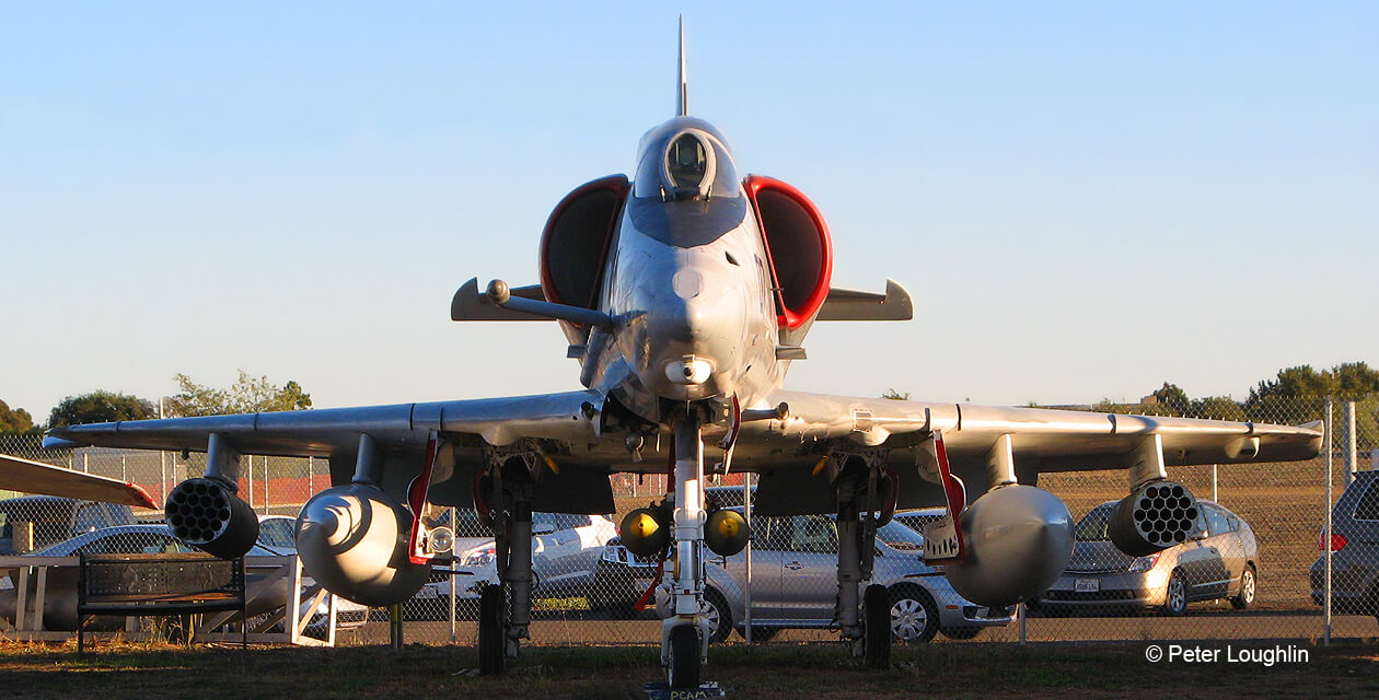 A-4E Skyhawk attack aircraft on the field at the Pacific Coast Air Museum. View is from directly in front. Pylons are filled with inert ordnance.