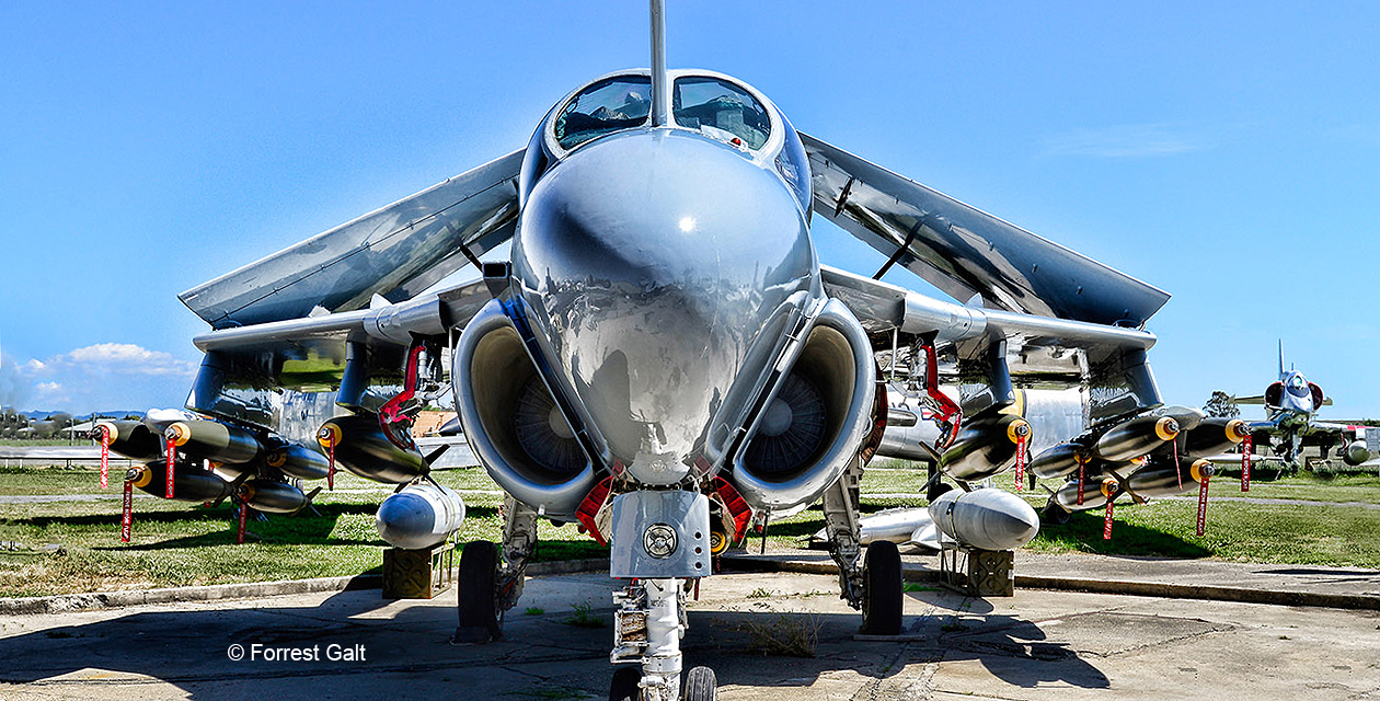 A-6E Intruder jet attack jet laden with inert bombs sits on the ground at the Pacific Coast Air Museum, wings folded