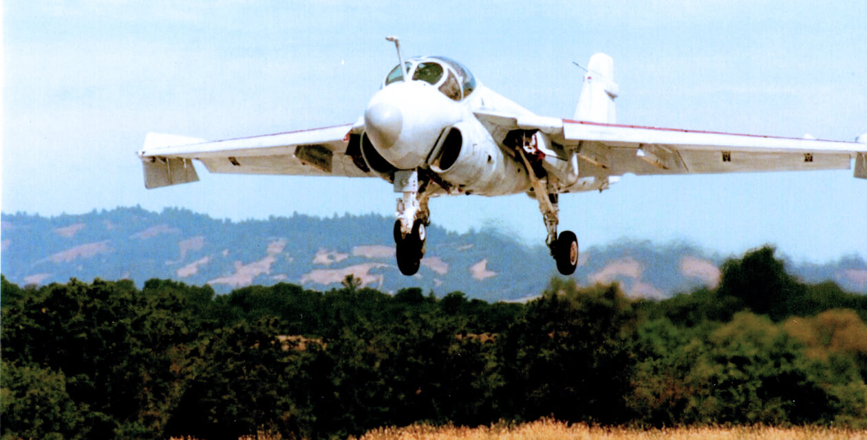 A-6E Intruder attack jet with wheels extended, about to land on an airport runway