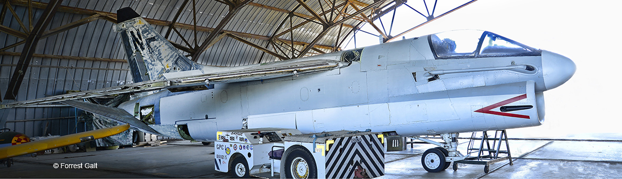A-7U Corsair II Jet attack aircraft under restoration inside a large hangar. Viewed from front right.