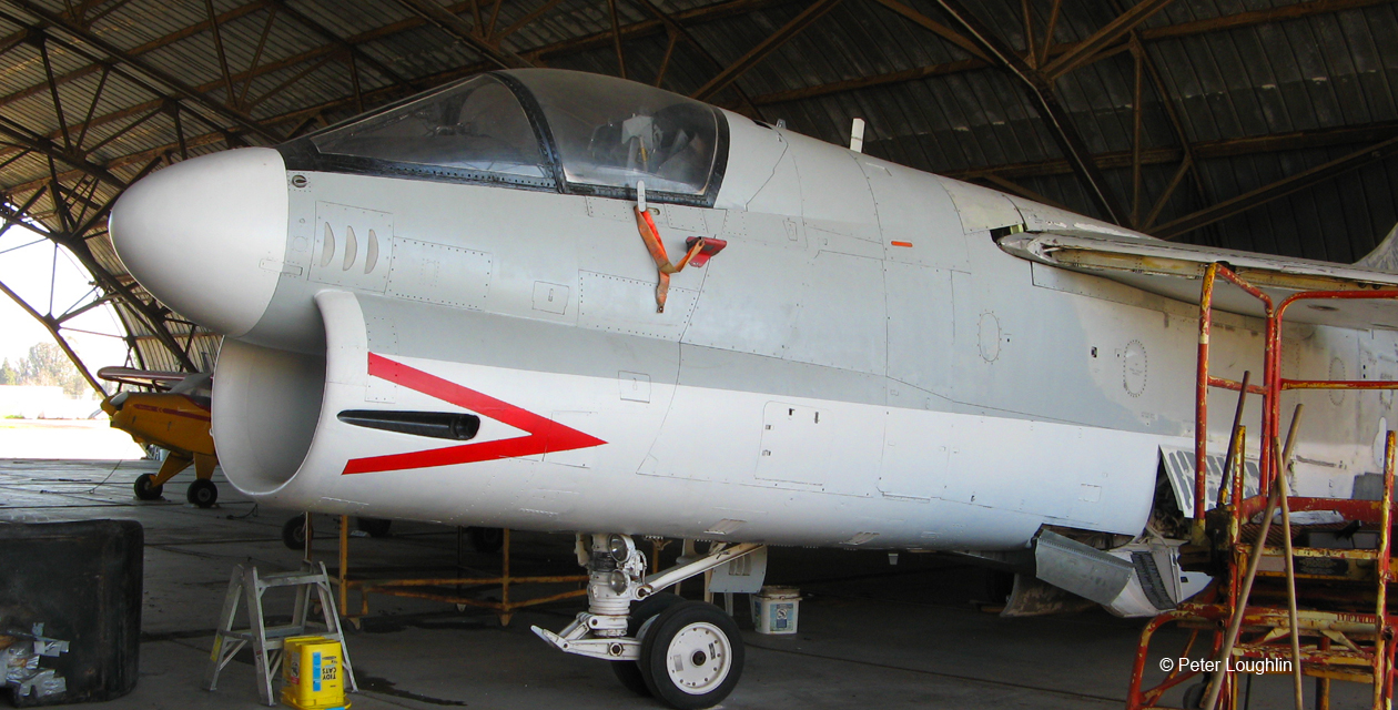A-7U Corsair II of the Pacific Coast Air Museum, photographed from the front left inside a large hangar.