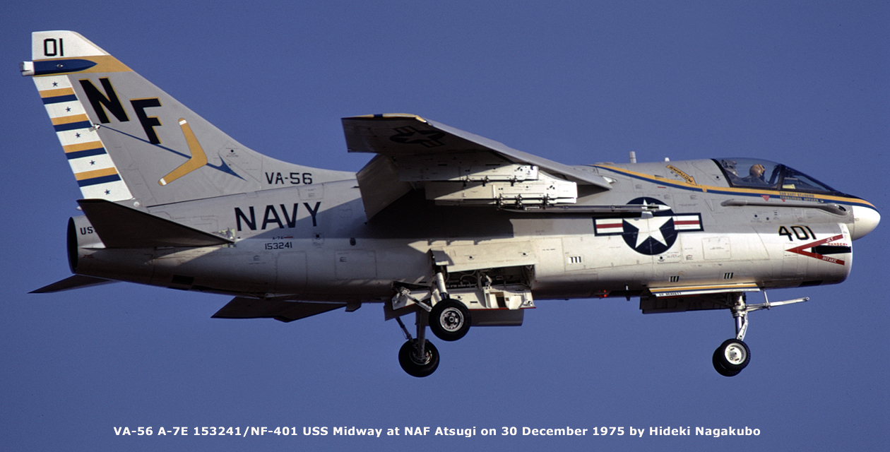 The Museum's A-7U Corsair II in flight during its service career. View from below and to the right, looking up at the side of the plane. Landing gear are extended.