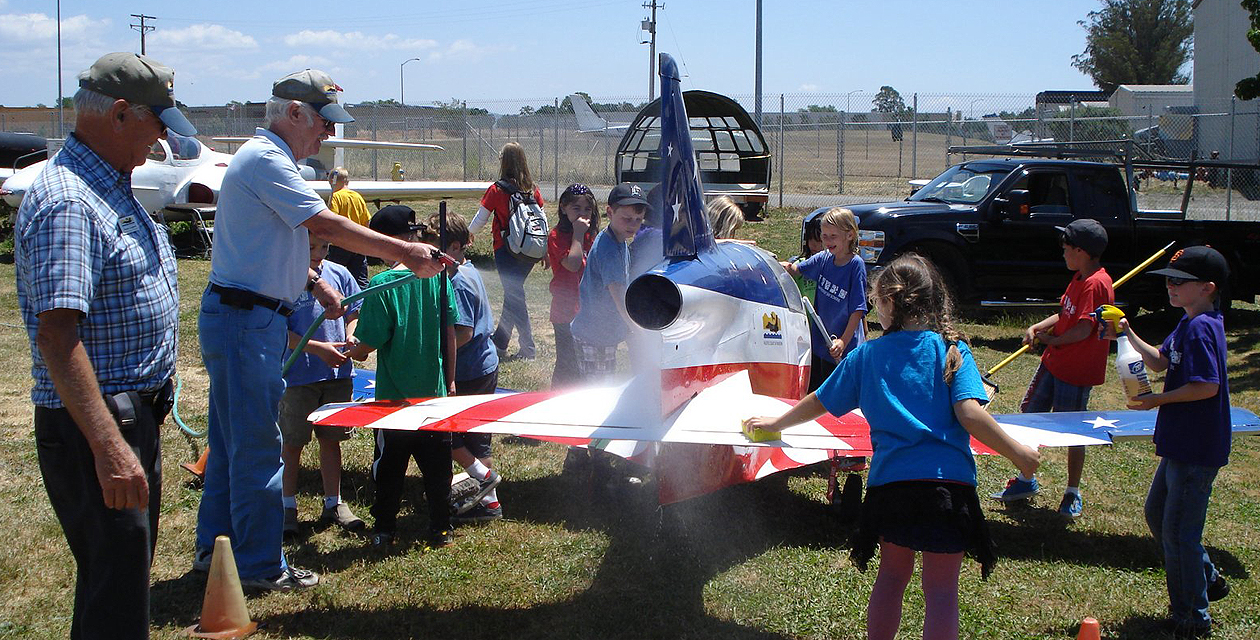 A group of schoolchildren wash a small Bede-5J jet aircraft as adults look on.