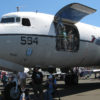 Close view of the nose of the C-118 Liftmaster, viewed from the ground. Air Show guests stand in the open cargo doors to watch the show.