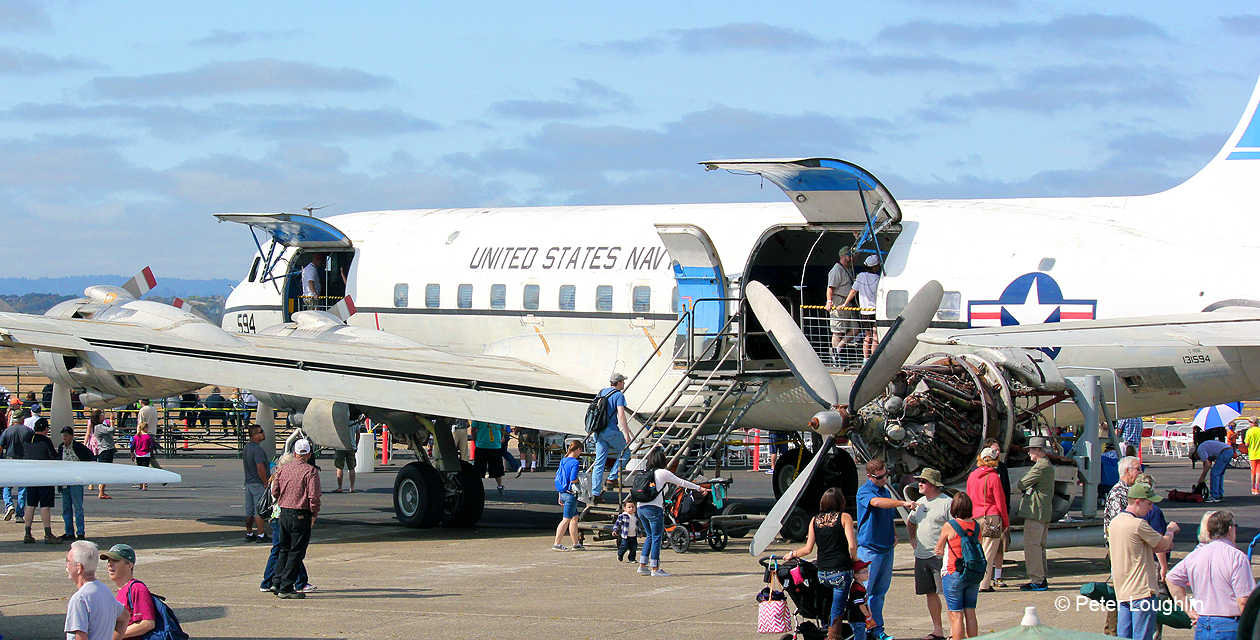 C-118 Liftmaster, viewed from the rear and to the left. This is at an air show, and guests stand around and in it.