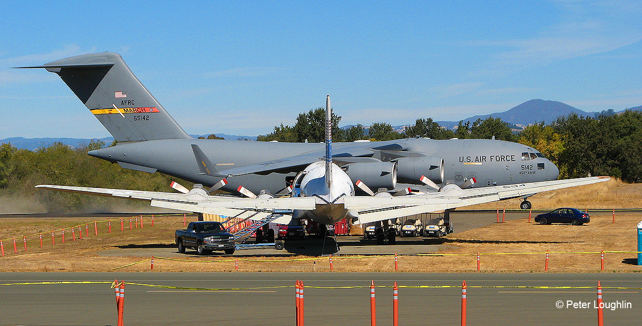 Distant view of C-118 transport from dead astern. A huge turbofan-powered C-17 Globemaster III taxis in front of her on its way to its parking spot