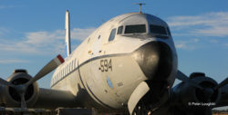 Early morning photo of first light on the side of the C-118 fuselage. Photo shows the nose of the plane from the front left.