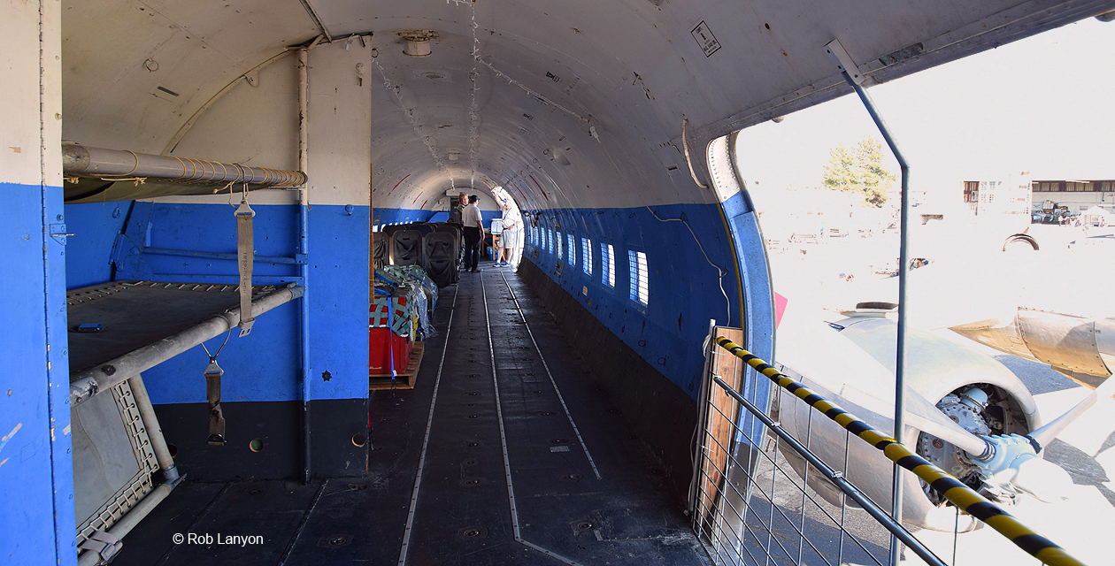 Interior of C-118 fuselage, looking aft from the front of the plane. The cargo door is open to the right, and you can see the left wing and engines.