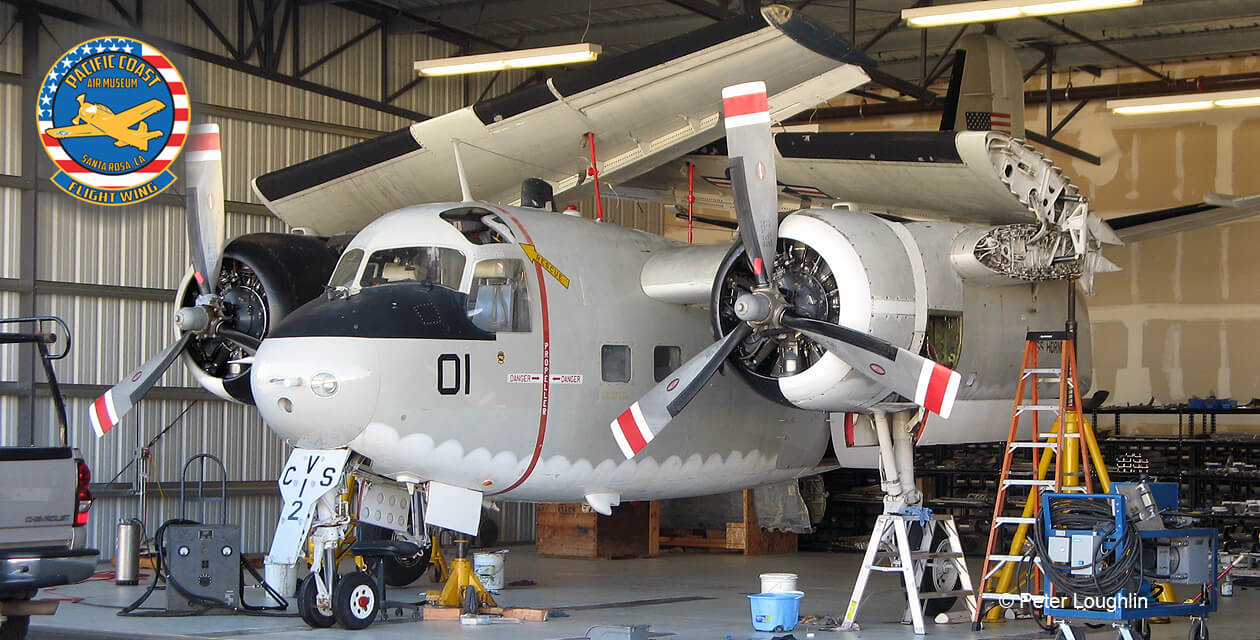 C-1A Trader in a hangar, wings folded, during a maintenance cycle. Photo is from in front and to the left.