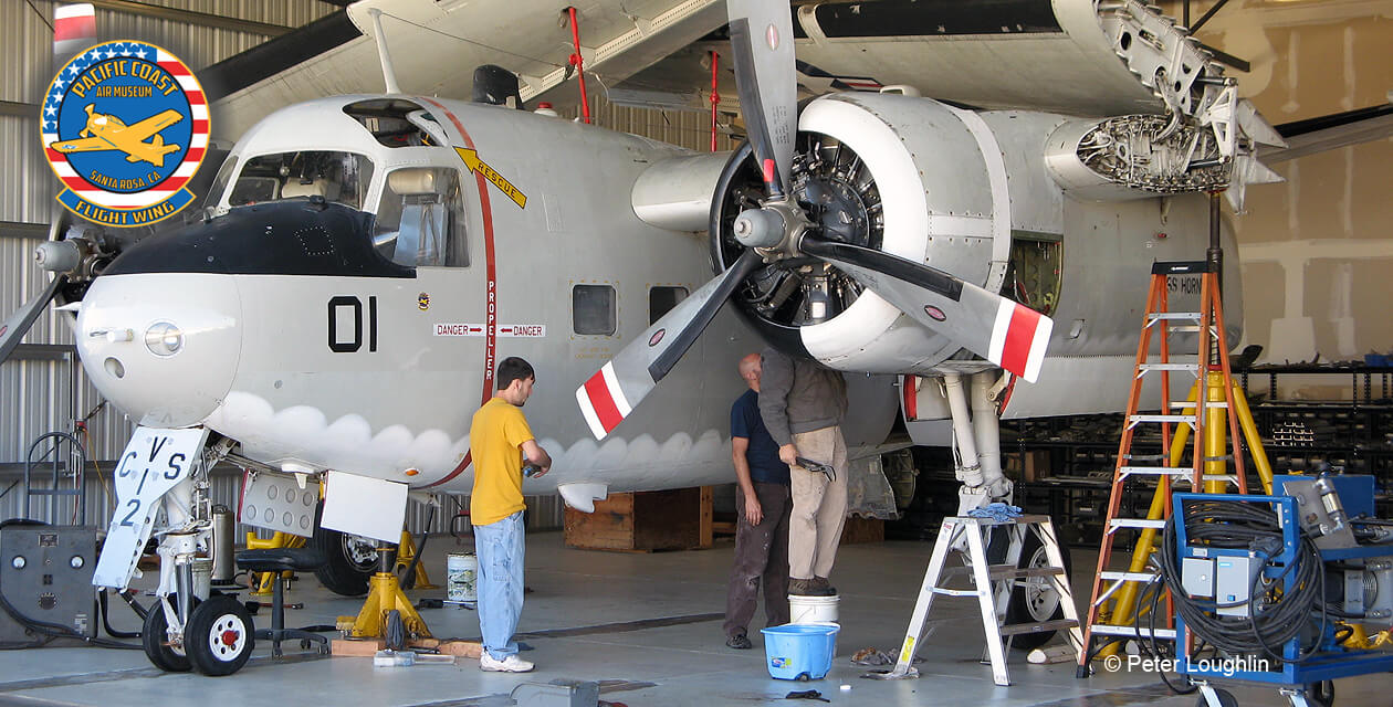 C-1A Trader with wings folded sits in a hangar for maintenance. Three crew members are working on the plane.