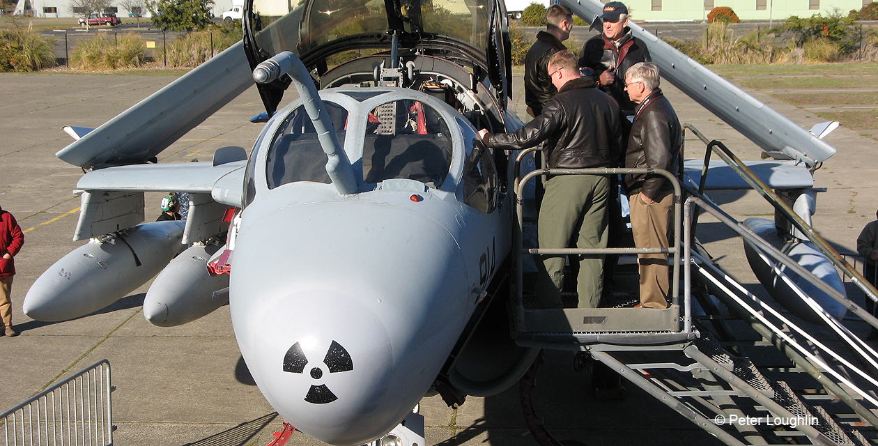High-angle photo of EA-6B prowler from the front, looking at the plane's nose. The canopies are up, air stairs have been pulled up to the cockpit and civilian spectators are looking into the cockpit.