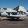 EA-6B Prowler photographed from the left side as it is towed past a curved-roof hangar on its way to the Wings Over Wine Country Air Show.