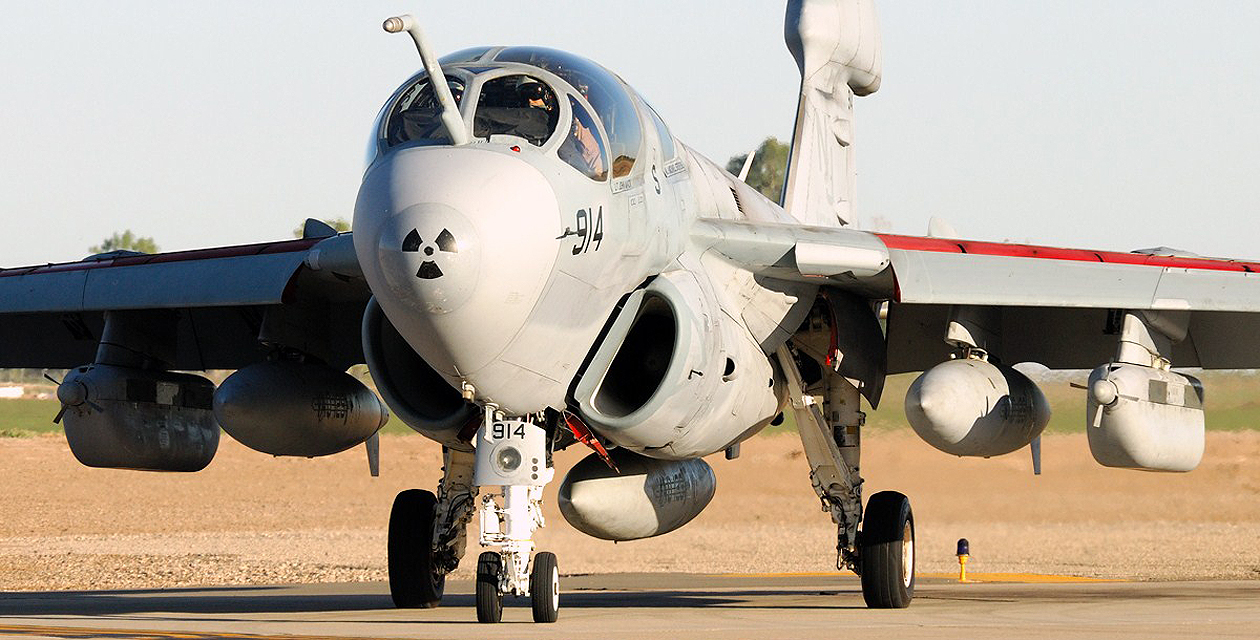 EA-6B Prowler during its active service life with the navy, taxiing under its own power on concrete taxiway at an unknown location.