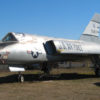 F-106 Delta Dart on the field at the Pacific Coast Air Museum, viewed from the left front. The sun is gleaming harshly off its shiny paint.