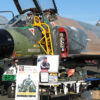 F-4C Phantom II on the ramp at the Wings Over Wine Country Air Show, with tables nearby displaying memorabilia of legendary ace Robin Olds.