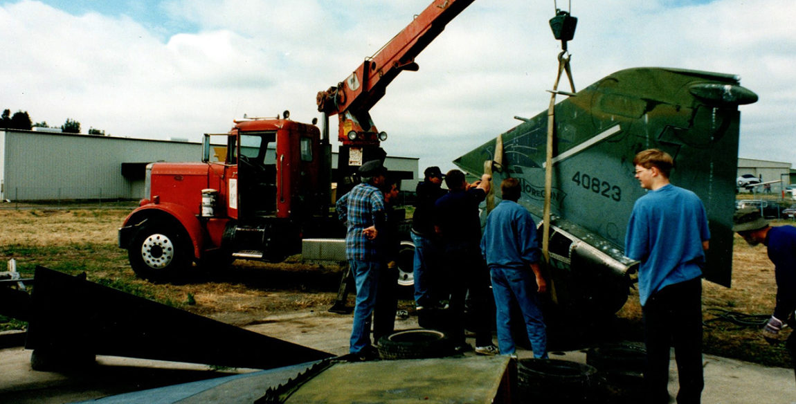 Old photograph of a crane truck unloading the parts of the F-4C Phantom II on the day the plane was delivered to the Pacific Coast Air Museum