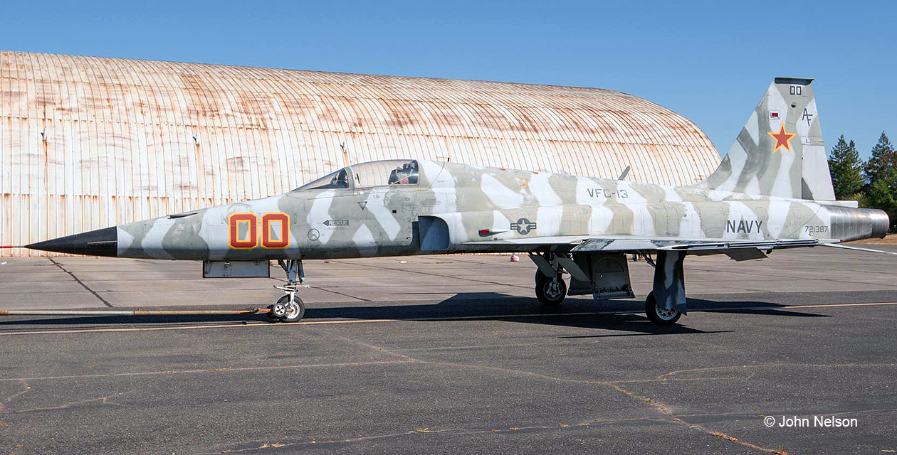 F-5E Tiger II jet fighter on the ramp near the Pacific Coast Air Museum. Broadside view of the left side. Paint scheme is alternating light gray and dark gray vertical tiger stripes, like some opposing aircraft our fighter pilots are likely to encounter.
