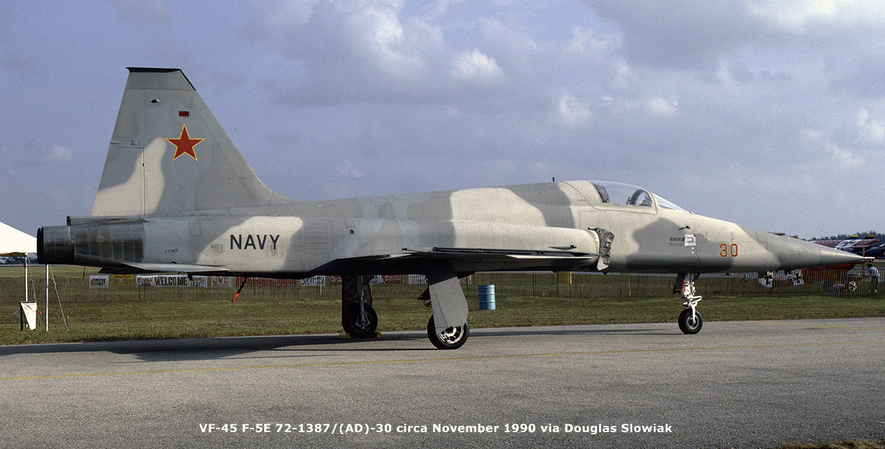 F-5E Tiger II painted in light gray and dark gray camouflage, with a red star on the tail. Broadside view of the right side, when she served with VF-45 around November 1990.