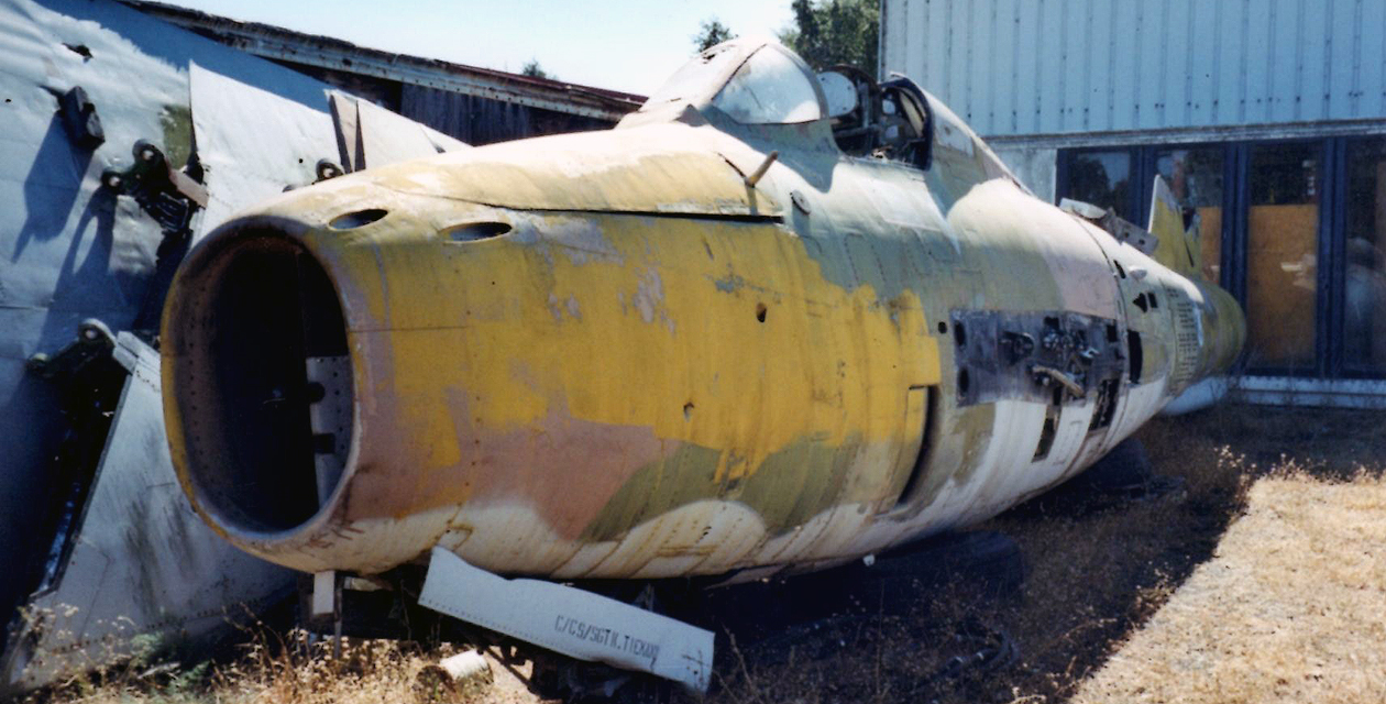 Fuselage of the Museum's F-84F jet fighter-bomber, with no wings and with badly faded paint. It sits derelict at a military depot, waiting to be used as a target.