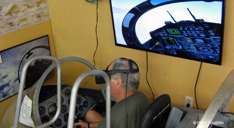 Photo of a man sitting inside the cockpit of a section of a small jet fuselage indoors. He wears 3D goggles and there is a large TV monitor on the wall showing the view he experiences as if he is flying an airplane.