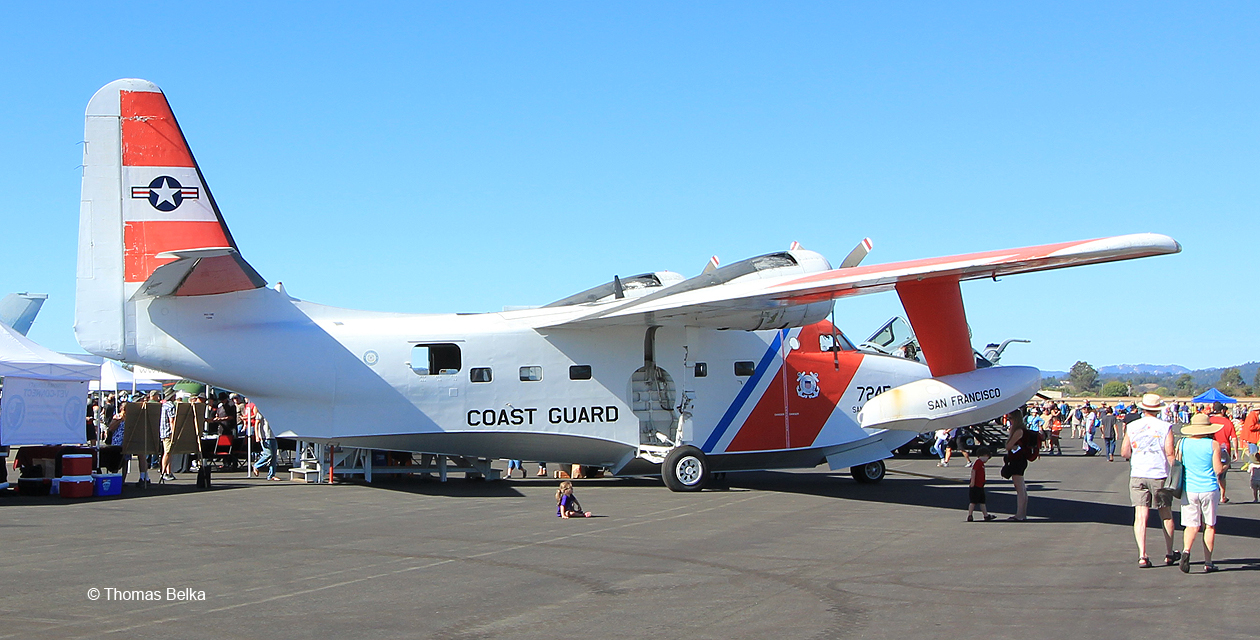 HU-16 Albatross sitting on the ramp during an air show, painted in US Coast Guard colors and viewed from the right rear.