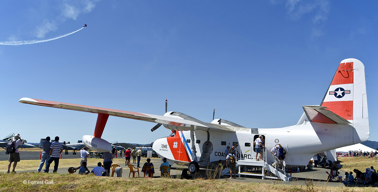 HU-16 Albatross painted in US Coast Guard colors, shown at the Wings Over Wine Country Air Show. People sit in the shade of its large wings, and an aerobatic plane lays a trail of smoke in the background.