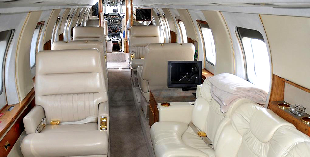 Interior view of the Lockheed Jetstar business jet, showing luxurious white leather seats and wood trim.