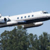 Lockheed Jetstar business jet making a low pass, with trees in the background.