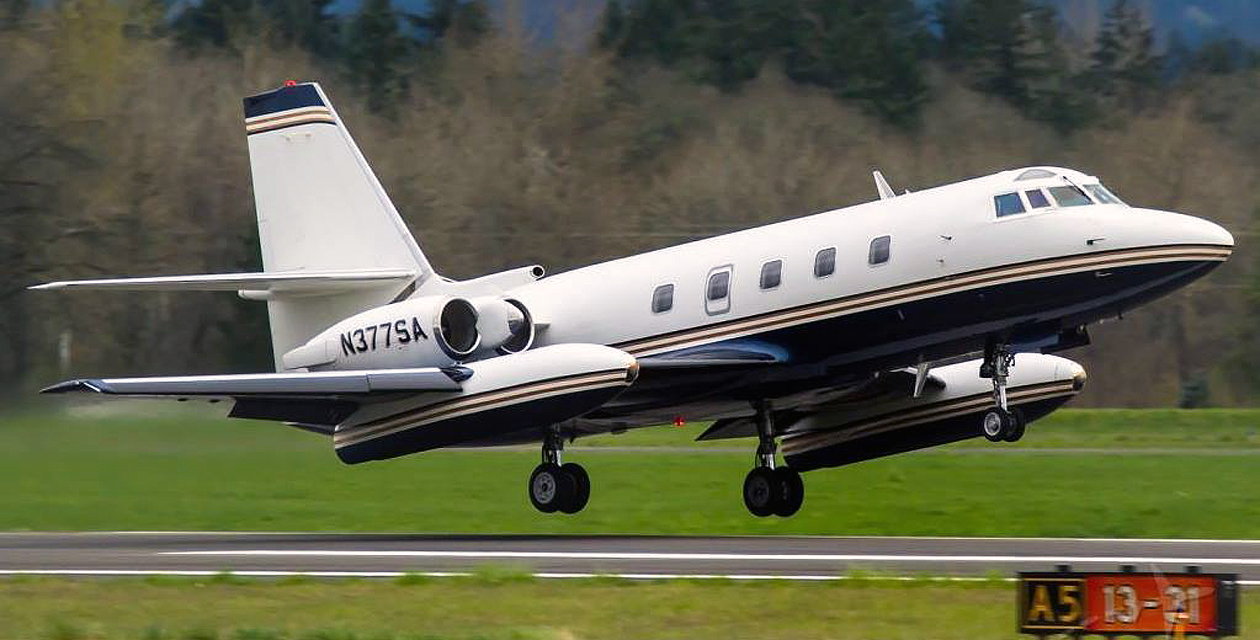 Lockheed Jetstar with its landing gear down and nose high, just about to touch down on a runway during landing.