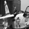 Black and White photo of an RF-86G Crusader on an aircraft carrier deck, with wingtips folded and canopy raised.