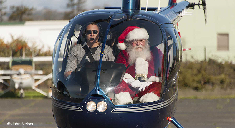 Santa Claus and a pilot sitting in a small blue helicopter which has just landed