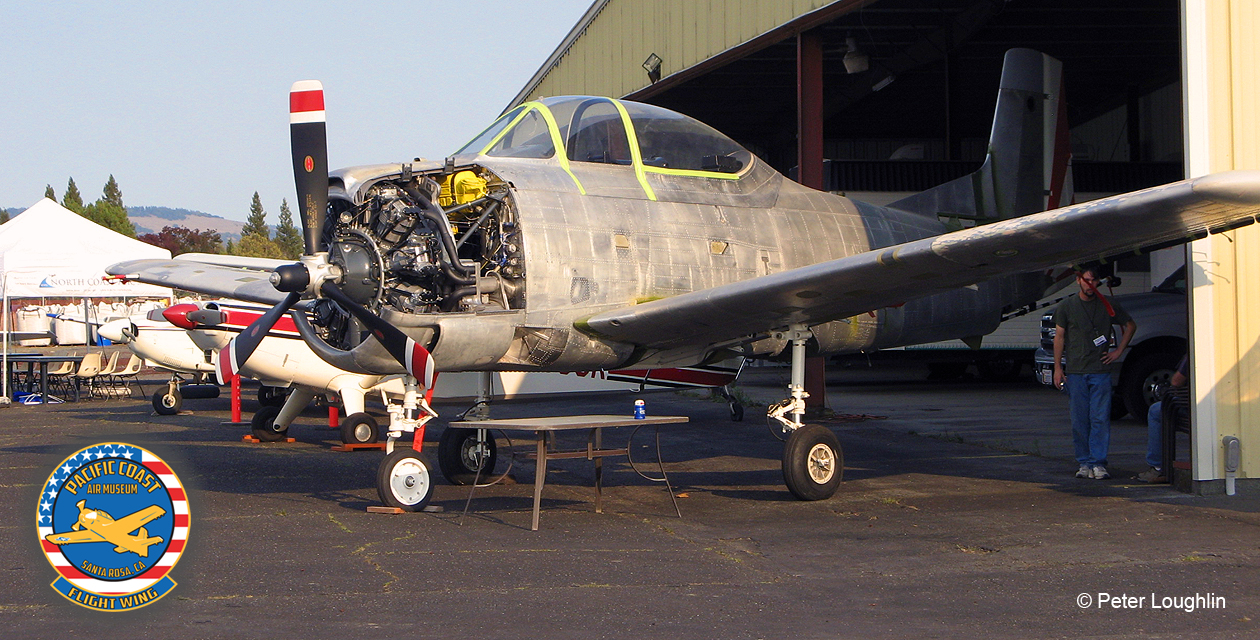 Photo of the T-28 in front of a hangar, with engine cowl panels removed.