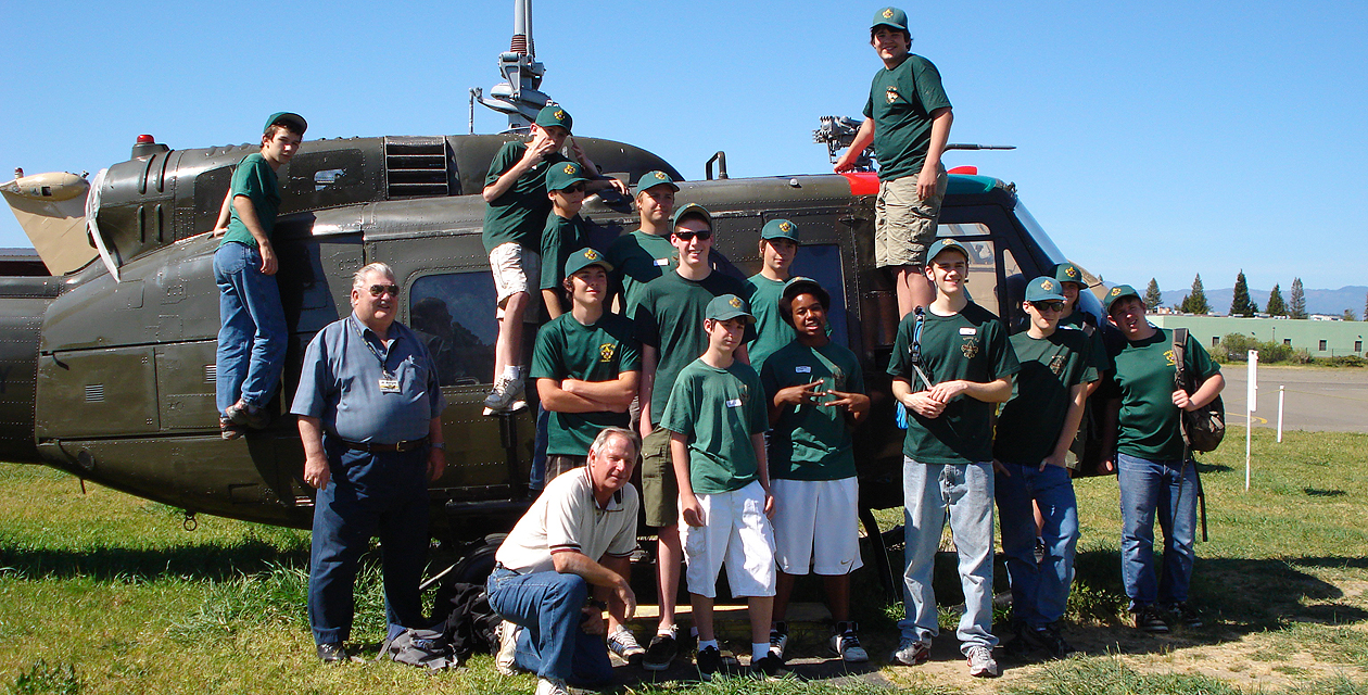 A group of boy scouts standing on and a the UH-1H Huey helicopter, smiling for the camera.