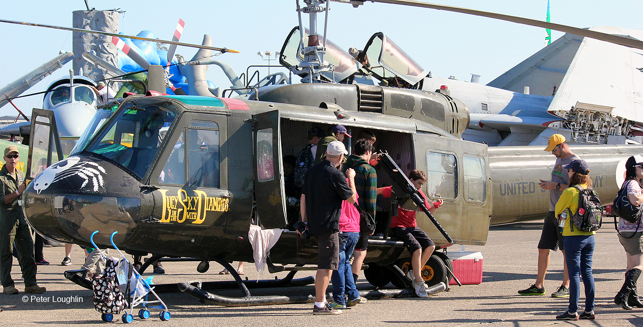 UH-1H Huey helicopter parked as a static display aircraft at an air show, with other planes parked around it and visitors climbing aboard.