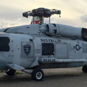 SH-60 Seahawk helicopter sitting on the ground with tail folded and no rotor blades