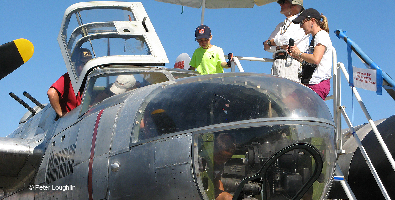 Close-up shot of A-26 Invader nose, from front right. Through the plexiglass windows you can see a young boy exploring the interior of the plane.
