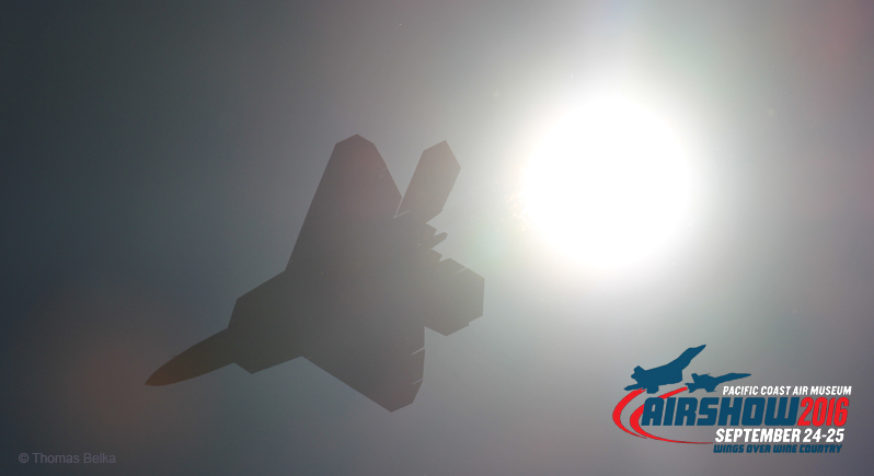 Silhouette of F-22 Raptor fighter aircraft flying past the sun, with Wings Over Wine Country Air Show logo in lower right