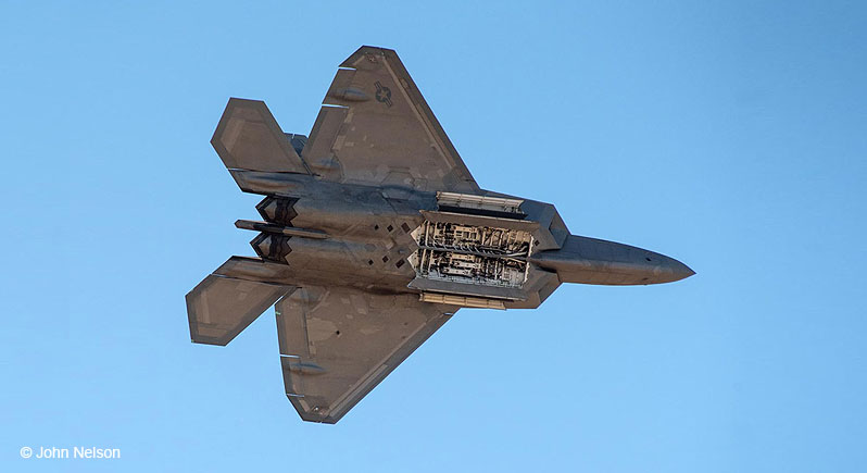F-22 Raptor fighter aircraft in flight, seen from below with weapons bay doors open