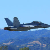F/A-18 Super Hornet makes a low pass. Hills are in the background. Heat distortion from hot exhaust blurs the background behind the plane's tail pipes.