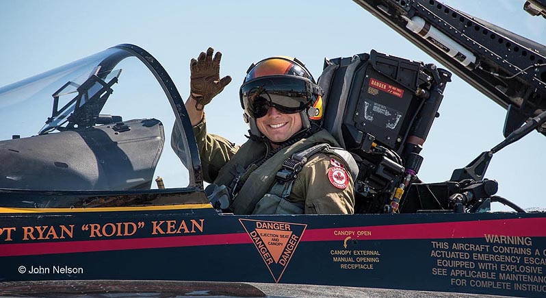 Close-up photo of Canadian Air Force demo pilot waving from the cockpit of his CF-18 fighter demo plane
