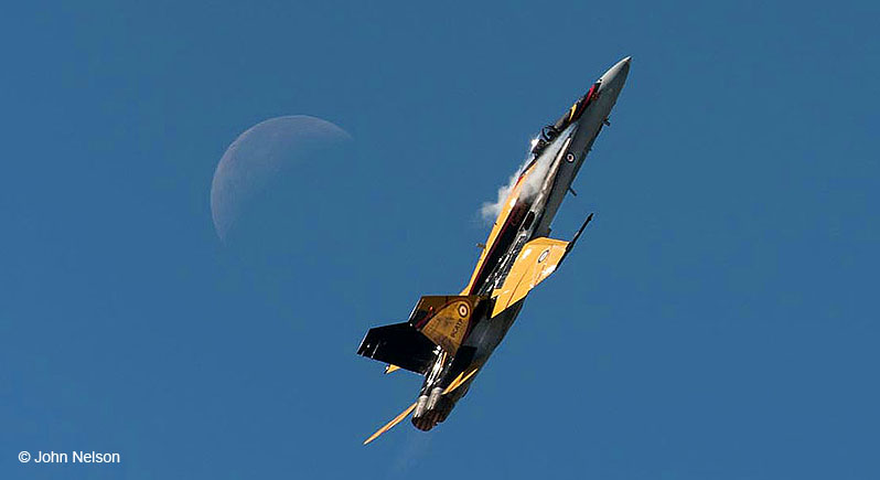 Yellow, black, and gray Canadian CF-18 demo plane in flight, zooming upward. The moon is behind and a little to the left.