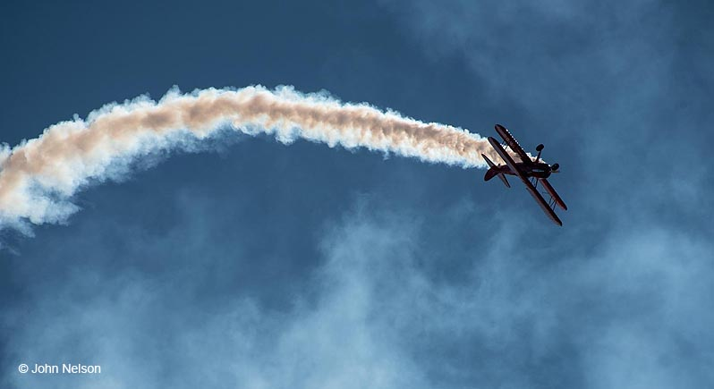 Red stunt biplane in flight, flying inverted, trailing a stream of white smoke.
