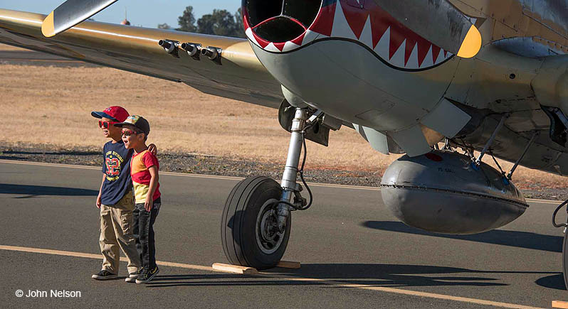 Two young children standing in front of a P-40 Warhawk for a photo