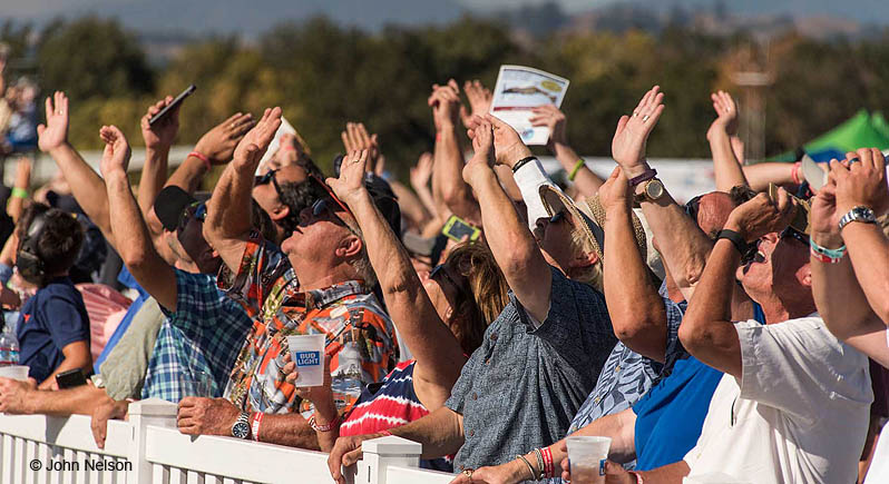 Crowd at an air show, lined up against the low flightline fence, holding hands up to shield their eyes from the sun.