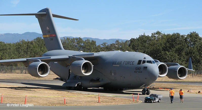Giant C-17 Globemaster III US Air Force transport plane parked on an airport ramp, with trees and hills in background
