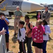 Children on the field at the Pacific Coast Air Museum, with a man explaining something to them.