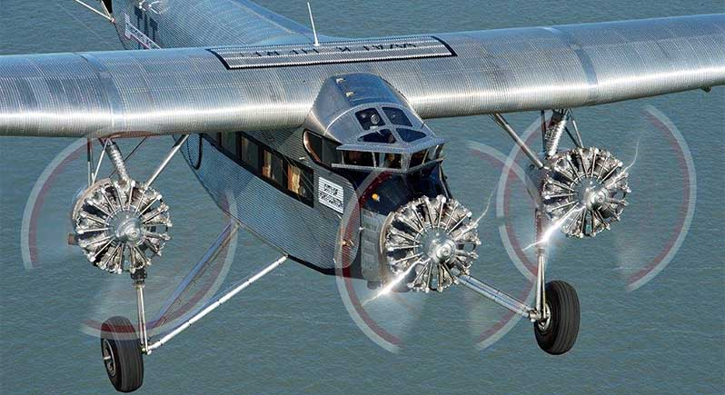 Antique Ford Tri-Motor aircraft in flight, viewed from above and to the front right