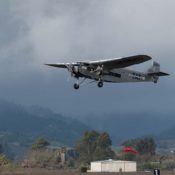 EAA 1929 Ford Tri-Motor takes off against dramatic cloudy skies