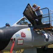 close-up view of the cockpit area of the F-106 Delta Dart, with canopy up and a visitor looking inside